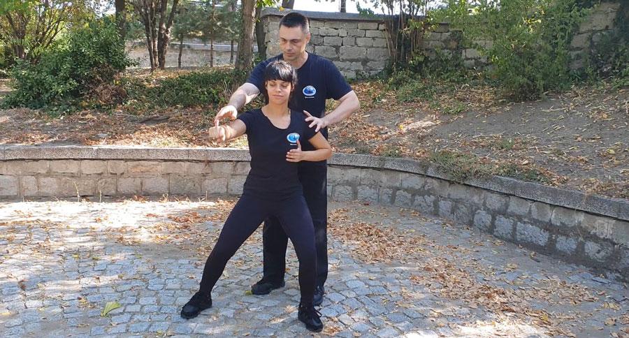 Учителят по Тай Чи коригира позицията на начинаещ